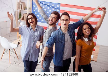 We are real patriots of our country. Cheerful young friends are standing and holding usa flag. They are looking at camera and smiling