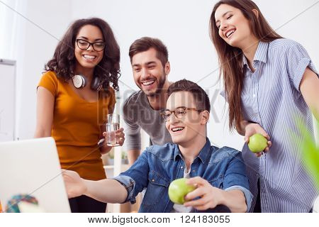 Cheerful young colleagues are making a break. They are looking at the laptop with joy and laughing. The man and woman are holding apples