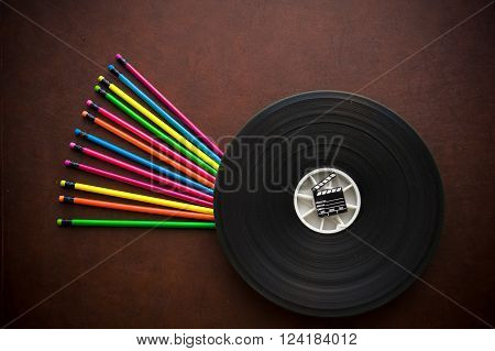 Wooden writer desktop with colorful pencil film reel and black movie clapper board