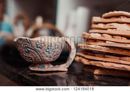 Products made of clay. Pottery of different sizes exhibited in shelf
