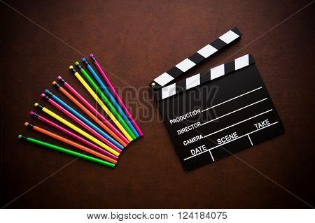 Wooden desktop with colorful pencil and movie clapper board