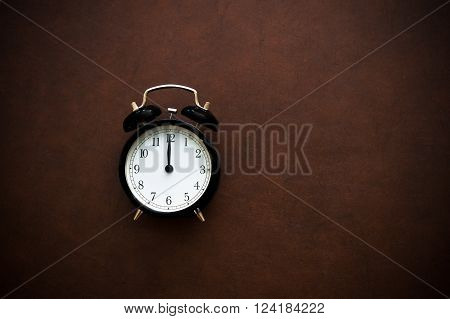 Vintage alarm clock reminder symbol on twelve o'clock hour on wooden background