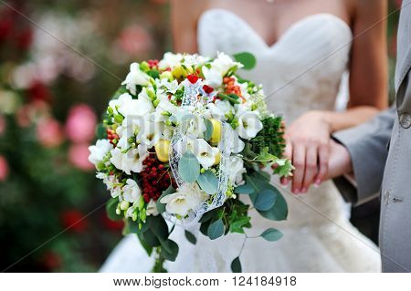 beautiful wedding bouquet at bride's hands outdoor