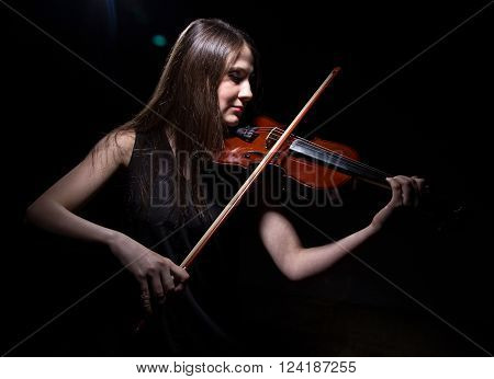 Young woman playing on violin on black background
