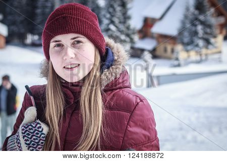 beautiful girl in a ski suit with skis