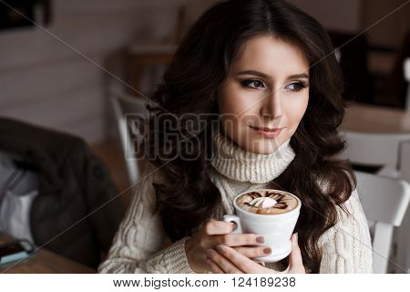 Nice sweet girl in white dress drinking coffee. Coffee beautifully decorated with a pattern. cup of latte coffee drinks decorated with latte art and pastry at cafe.
