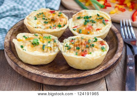 Mini quiche with chicken and bell pepper on a wooden plate