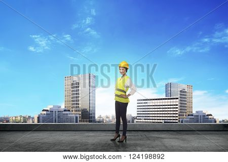 Asian woman in safety vest posing. Female architect concept