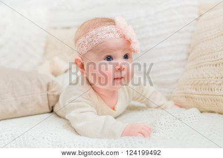 Amazed cute little baby with chubby cheeks wearing white clothes and pink band with flower lying on bed with knitted pillows. Babyhood and childhood concept