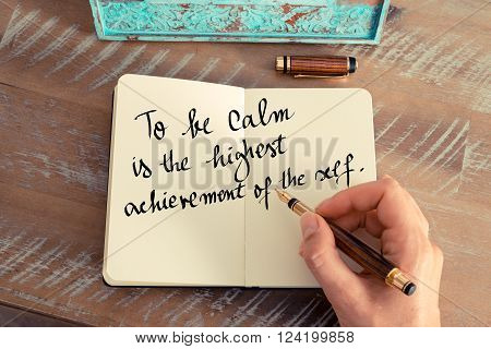 Retro effect and toned image of a woman hand writing on a notebook. Handwritten zen proverb To be calm is the highest achievement of the self as inspirational concept image