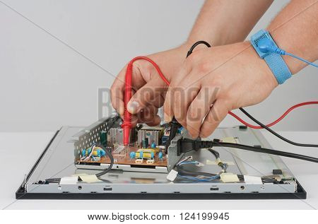 Man doing the measurement of the voltage in the LCD display.