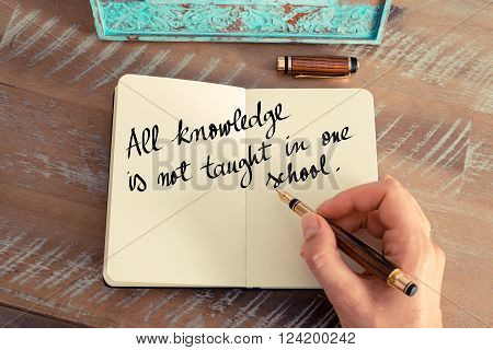 Retro effect and toned image of a woman hand writing on a notebook. Handwritten quote All knowledge is not taught in one school as inspirational concept image
