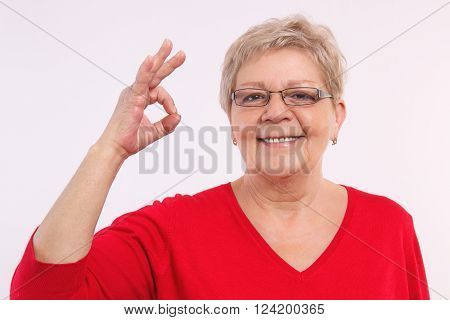 Happy smiling elderly woman showing sign ok, approval of offer or situation, showing positive human emotions, facial expressions