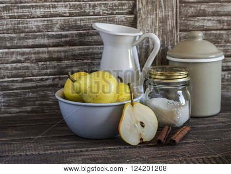 Fresh pears in bowl cinnamon sugar and vintage crockery on a dark wooden background. Kitchen still life in rustic style