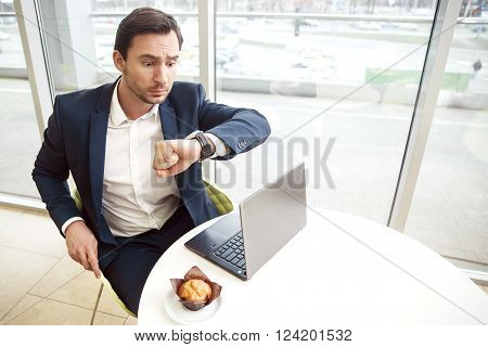 You mast hurry up. Handsome surprised businessman sitting at the table and looking at his wrist watch while expressing wonder