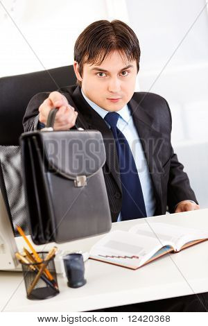 Attentive business man sitting at office desk and giving briefcase