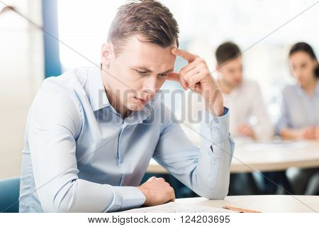 Mull it over. Pleasant serious man sitting at the table and being involved in thinking while his team sitting in the background and discussing a project