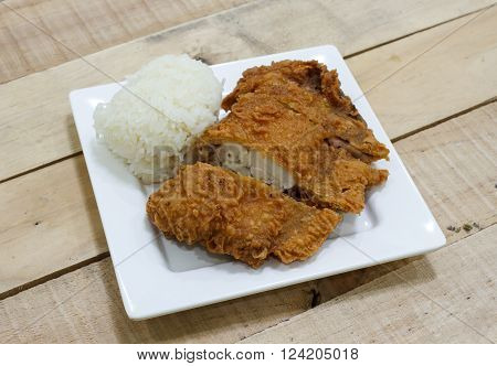 Crispy fried chicken and sticky rice on wooden table