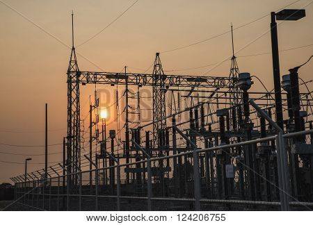The high voltage equipment in the outdoor electrical substation yard during sunrise ** Note: Visible grain at 100%, best at smaller sizes