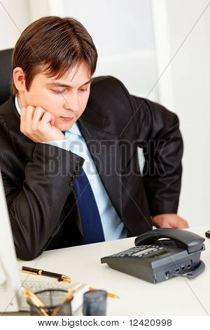 Concentrated business man sitting at office desk and expecting phone call