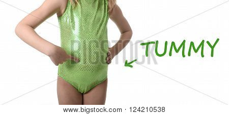 6 or 7 years old little girl posing isolated on white background pointing tummy in learning English language school education body parts card set