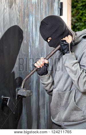 a burglar breaking open of a padlock metal door