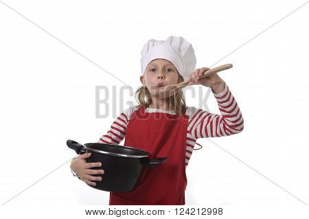 6 or 7 years old little girl in cooking hat and red apron playing cook smiling happy holding pot and pretending tasting food with spoon isolated on white background looking excited