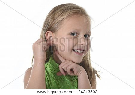 blond beautiful junior schoolgirl pointing her ear smiling happy isolated on white background ** Note: Soft Focus at 100%, best at smaller sizes