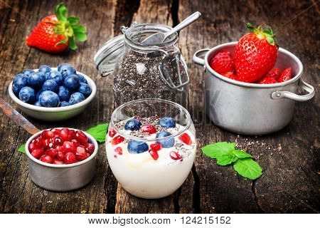 Yogurt, berries, chia seeds, healthy breakfast on old wooden table