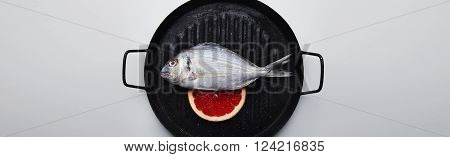 Close Up Presentation Of Fresh Wild Sea Bream On Grill Pan, With Grapefruit Slice Below, Ready To Co