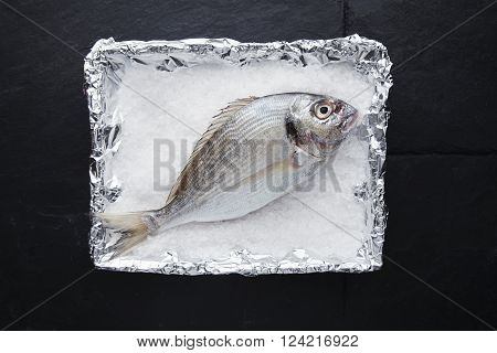 Presentation Of Fresh Wild Sea Bream In Foil Metallic Paper Filled With Stone Salt Grains, Ready To