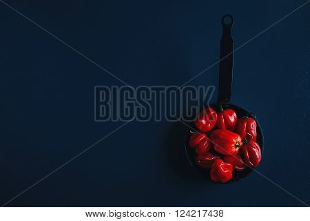 Fresh mini red bell peppers in vintage small iron cast pan, top
