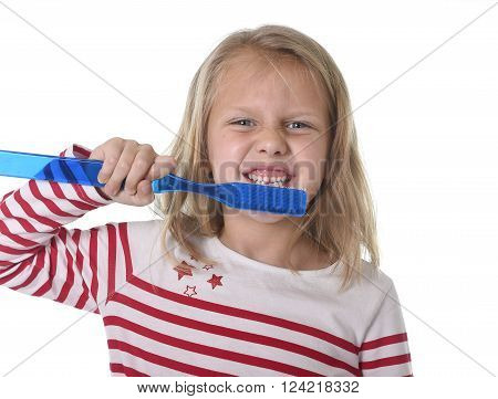 sweet beautiful 6 to 8 years old female child with blond hair and big blue eyes holding huge toothbrush smiling happy in dental care and healthy lifestyle education concept isolated white background