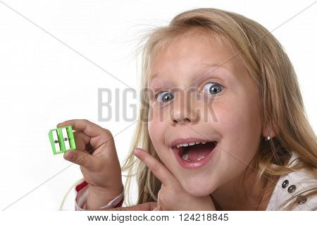sweet beautiful female child 6 to 8 years old with cute blonde hair and blue eyes holding drawing pencil sharpener isolated on white in education and primary or junior school supplies concept