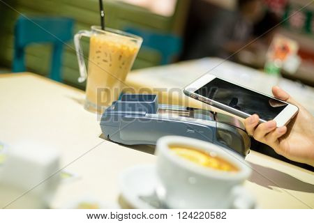 Woman using mobile phone to pay the biil with NFC technology