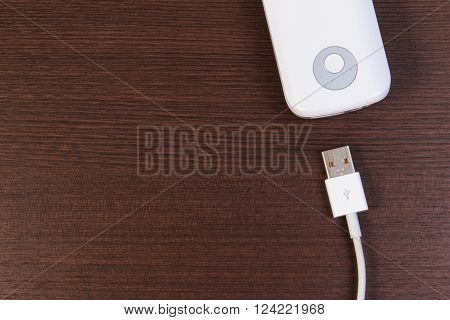 Usb Cable Charger With Energy Bank On Wooden Table.