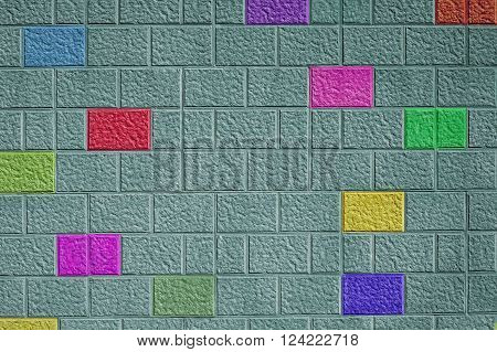 Painted green brick wall background with different colored bricks abstract pattern colorful fun design.