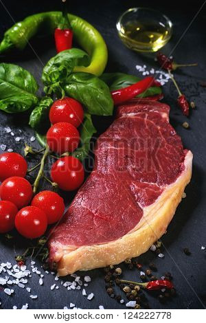 Raw steak with vegetables over black stone background
