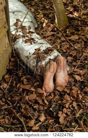 Wrapped Barefoot Corpse Lying In The Woods