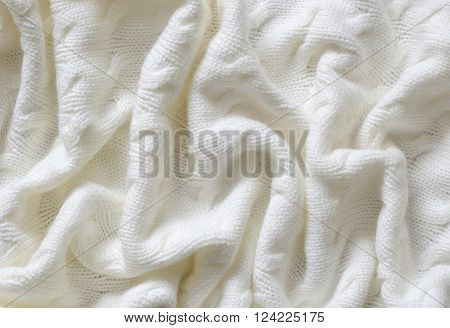 Closeup of crumpled white knitted blanket for background