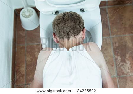 Young Boy Vomiting Into A Toilet Bowl