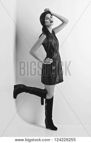 Beautiful young woman with dark lips and ponytail in fancy leather dress standing near white wall. Copy space.