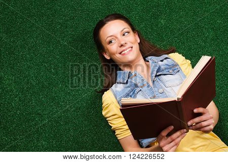 Young woman is lying down on a grass,thinking about something while reading book.