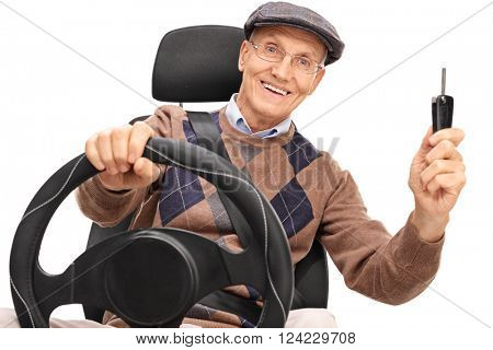 Senior man holding a steering wheel and a car key isolated on white background