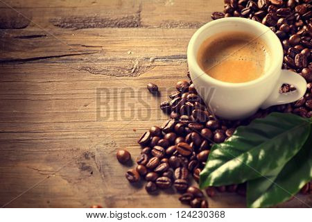 Coffee. Cup Of Espresso Coffee on wooden background decorated with coffee beans and green leaf of coffee plant. Copy space for your text. Vintage sepia toned