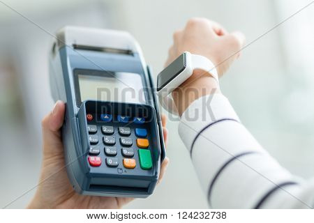 Woman using smartwatch to pay the bill