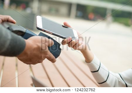 Woman pay by mobile phone on pos machine