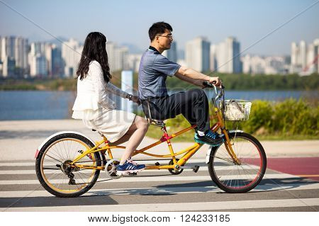 SEOUL KOREA - APRIL 24 2015: Young couple cycling at a racreation park zone on the bank of Hangang river in Seoul Korea