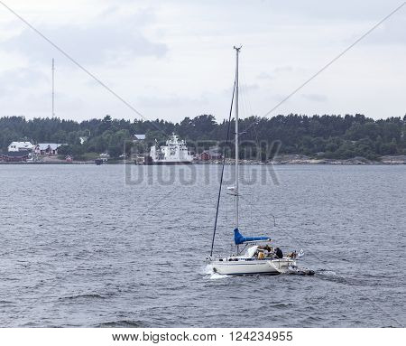 BALTIC SEA, ALAND ON JUNE 27. View of a sailboat pass the viewer on June 27, 2013 at The Baltic Sea, Aland. Unidentified people on board. Overcast. Harbor in the background. Editorial use.