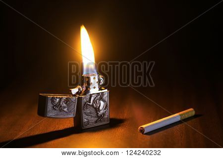 Beautiful Lighter And Cigarette On A Wooden Floor And Lighter's Fire Is Igniting The Dark Enviroment